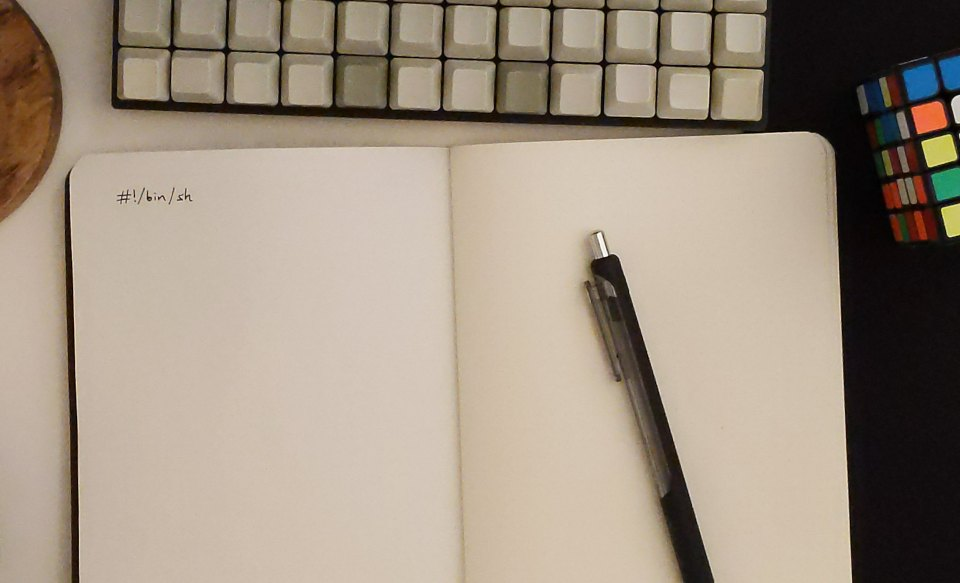 Cover image: Photo of small mechanical keyboard and notebook with  only #!/bin/sh written in it